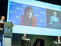 Podium with live speakers and speakers connected virtually through a huge screen placed on the podium