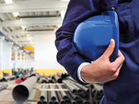 A person is holding a blue safety helmet unter the arm.